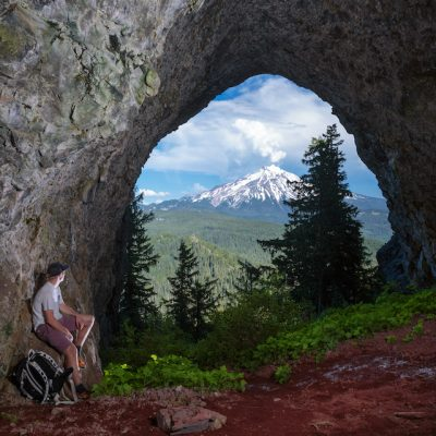 James Engerbretson admiring the picturesque framing of nearby Mount Jefferson from inside the Boca Cave on Triangulation Peak in central Oregon.  The floor of the large, single chamber cave is covered in a beautiful red soil and is complimented by a leafy green bed outside the entrance.