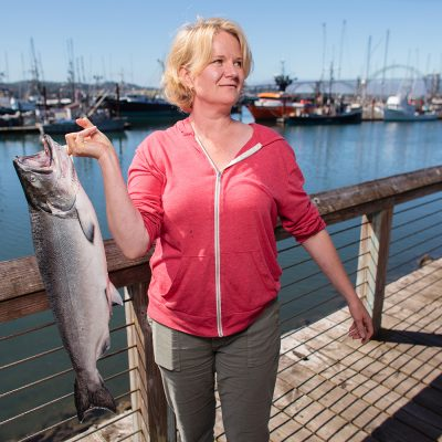 Laura Anderson, holding fresh salmon in front of Newport's fishing fleet, grew up fishing with her dad who was a commercial fisherman. Anderson opened her restaurant and market, Local Ocean, over a decade ago.