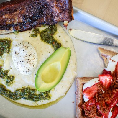 Weekend brunch at Portland's popup HunnyMilk features dishes like this crispy pork ribs with cheesy garlic grits, slow poached egg, avocado and chimichurri sauce on the left combined with graham cracker waffle dipped in honey butter with cheesecake mousse, chambered strawberries and brown butter bits.