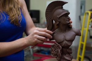 Allison Brown hands working clay of USC Trojan